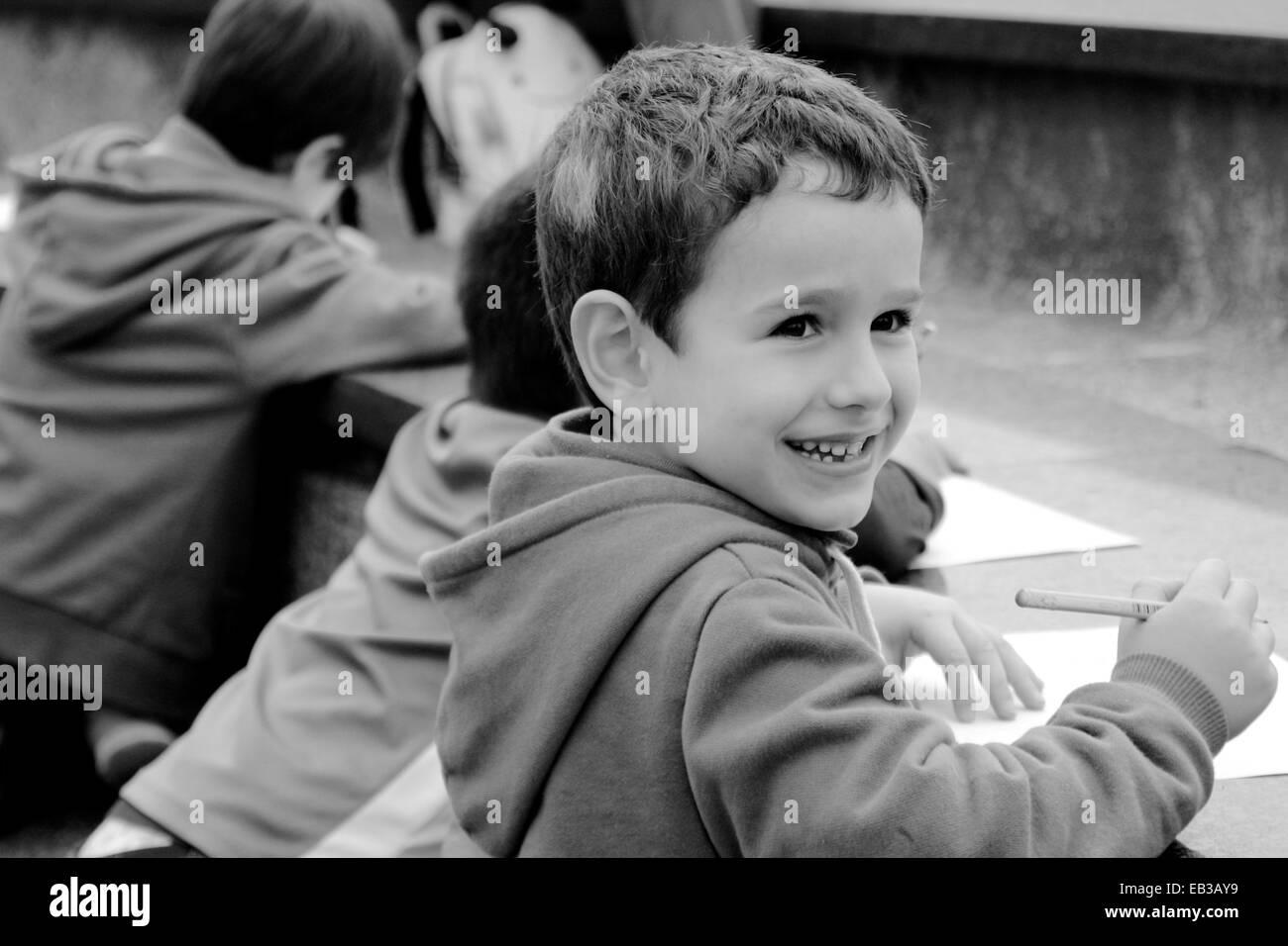 China, Hong Kong Island, Hong Kong, Boy (4-5) smiling while drawing, people in background - Stock Image