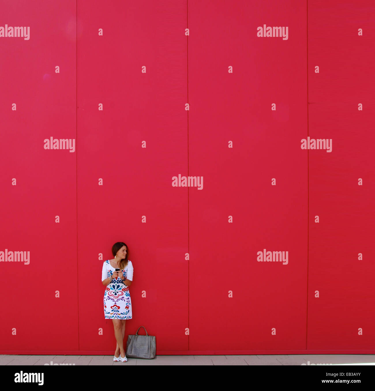 Woman standing in front of a red wall text messaging - Stock Image