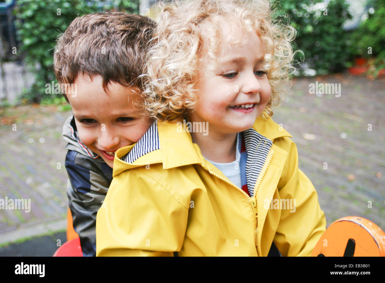 Smiling Boy and girl sitting on spring ride in playground - Stock Image