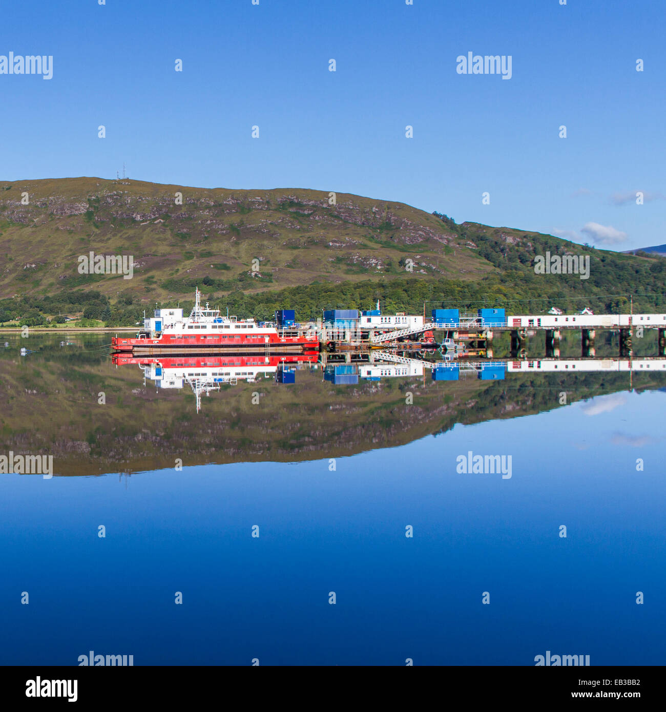 UK, Scotland, View of harbor and hill reflecting in water - Stock Image