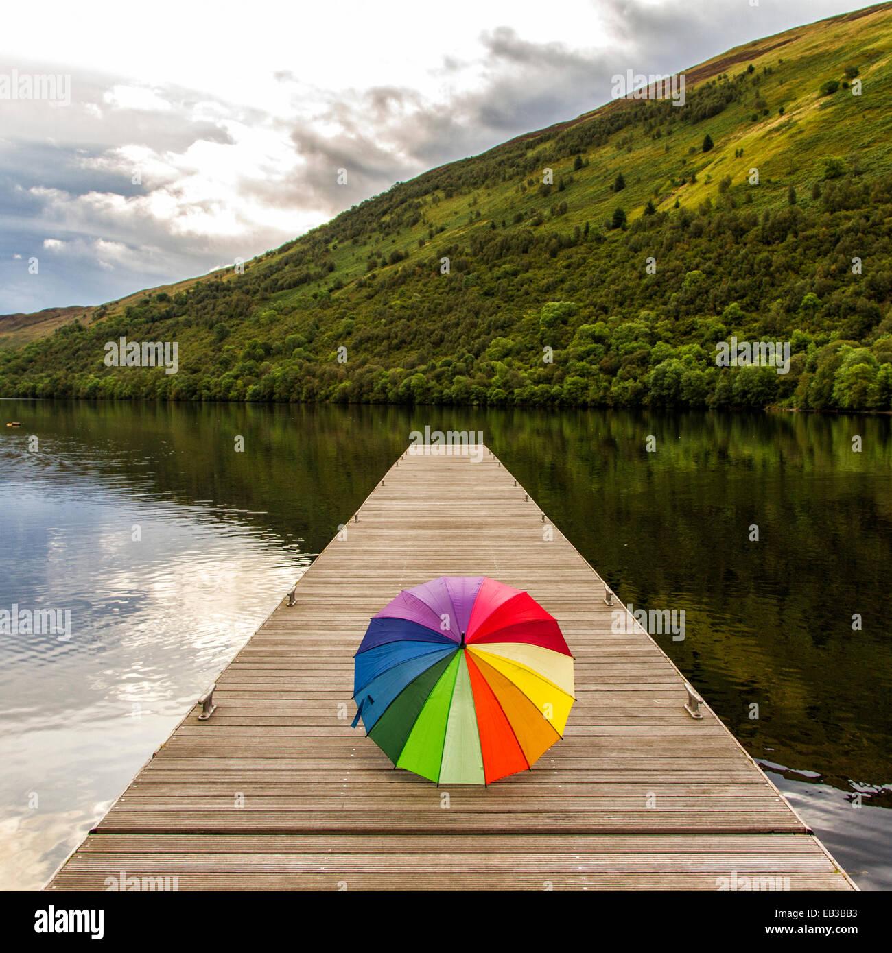 UK, Scotland, Multicolored umbrella on jetty - Stock Image