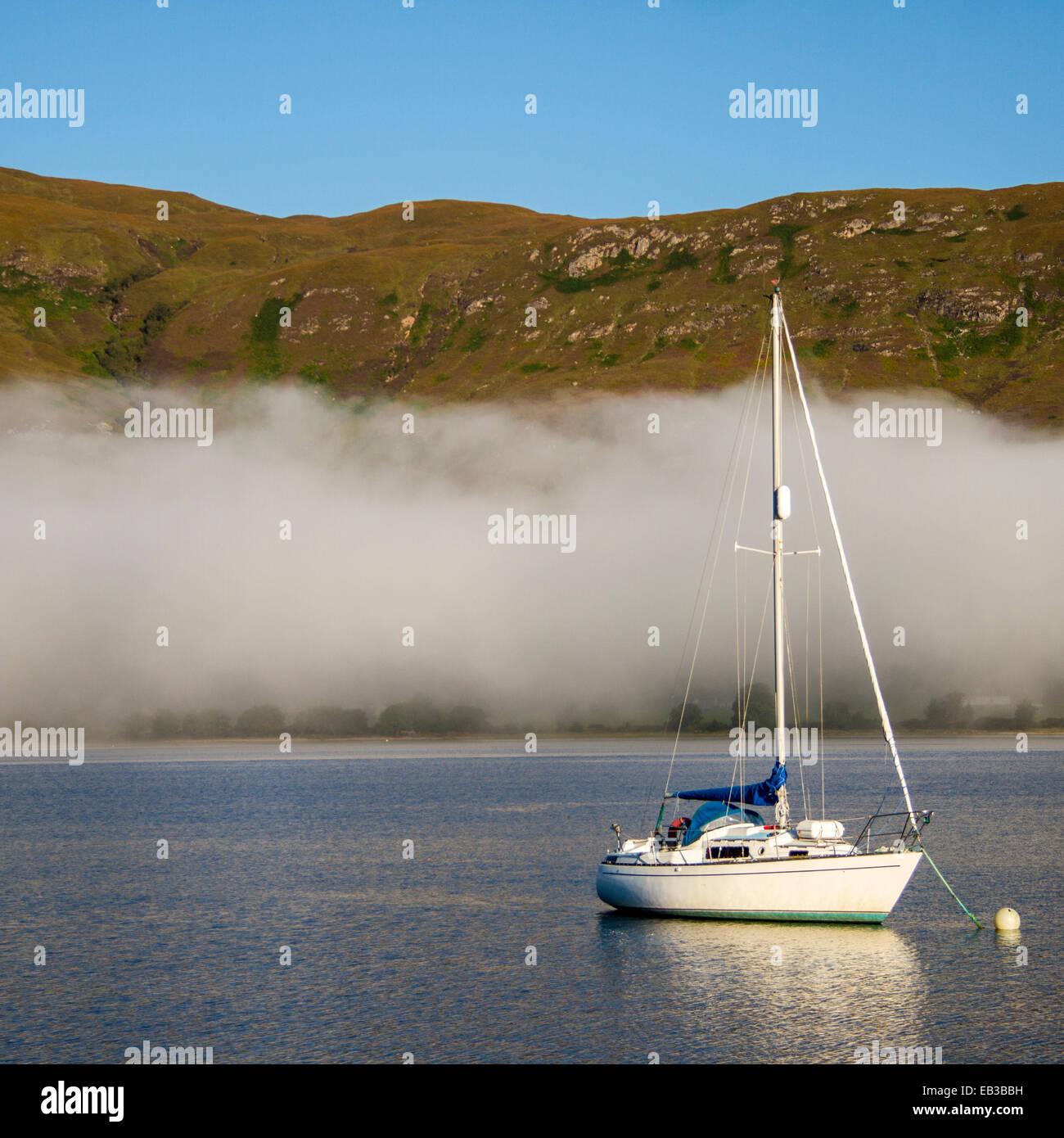 UK, Scotland, Sailboat on loch with fog - Stock Image