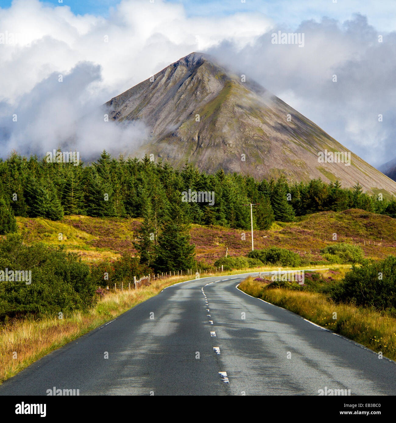 UK, Scotland, Isle of Skye Road among plain leading towards mountains - Stock Image
