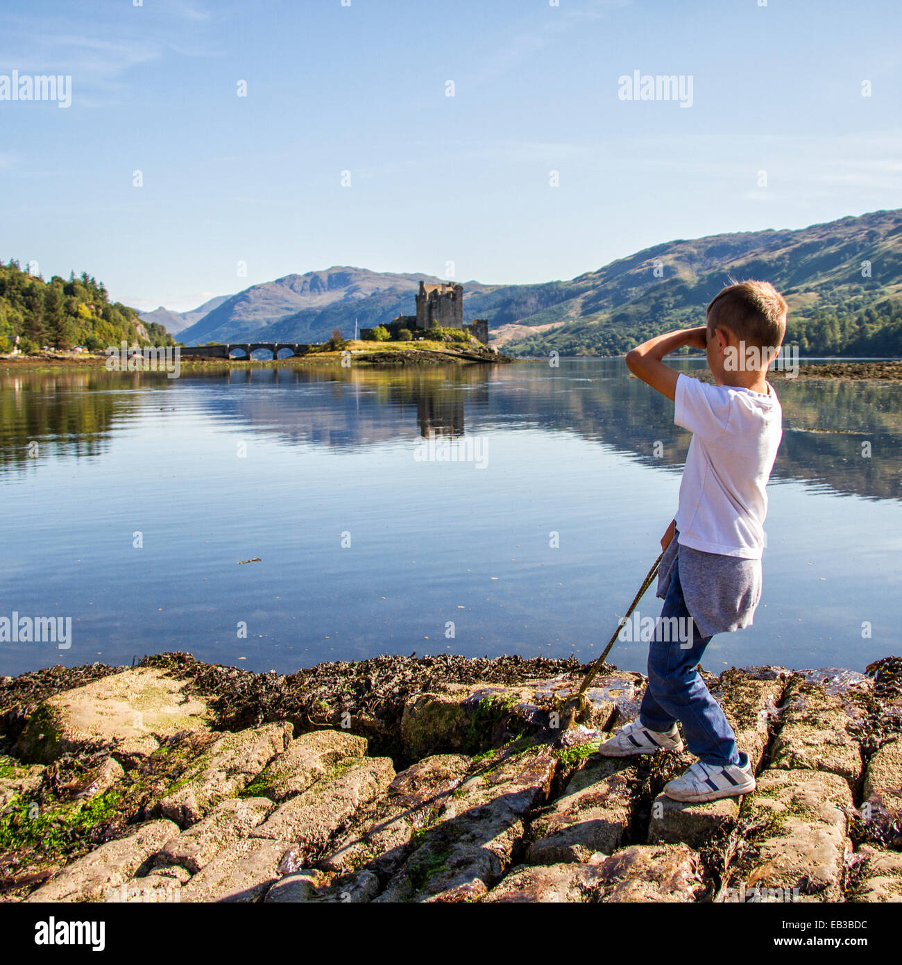 UK, Scotland, Boy (6-7) looking at Eileen Donan Castle - Stock Image
