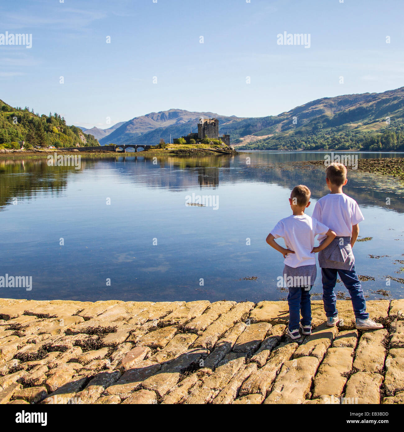 UK, Scotland, Boys (6-7) looking at Eileen Donan Castle - Stock Image