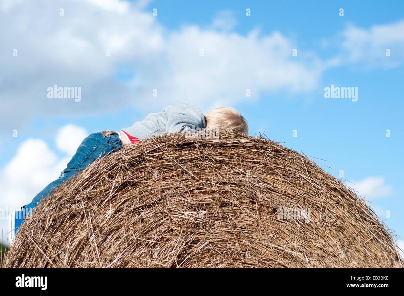 Boy lying on hay bale - Stock Image