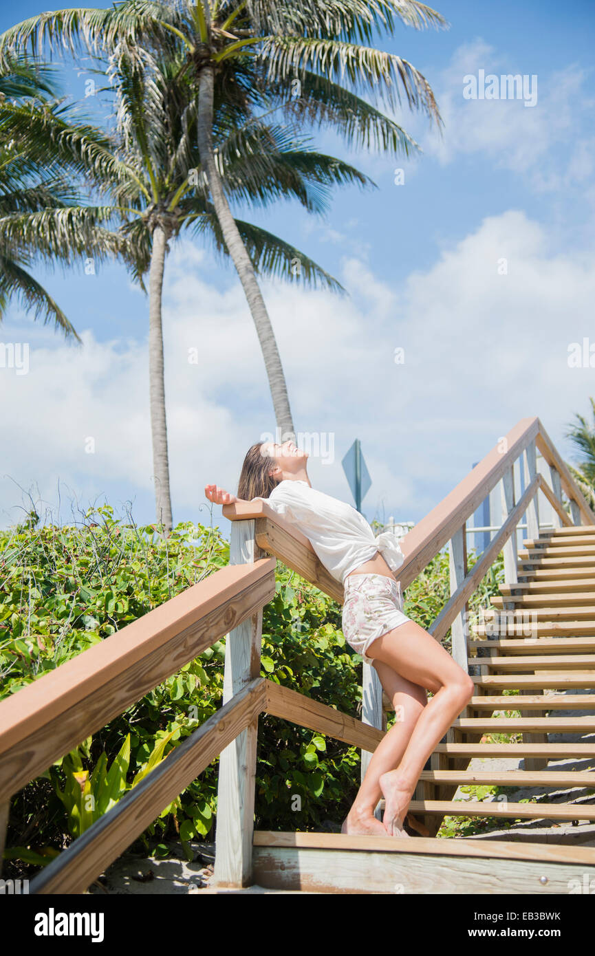 Caucasian woman standing on wooden staircase Stock Photo