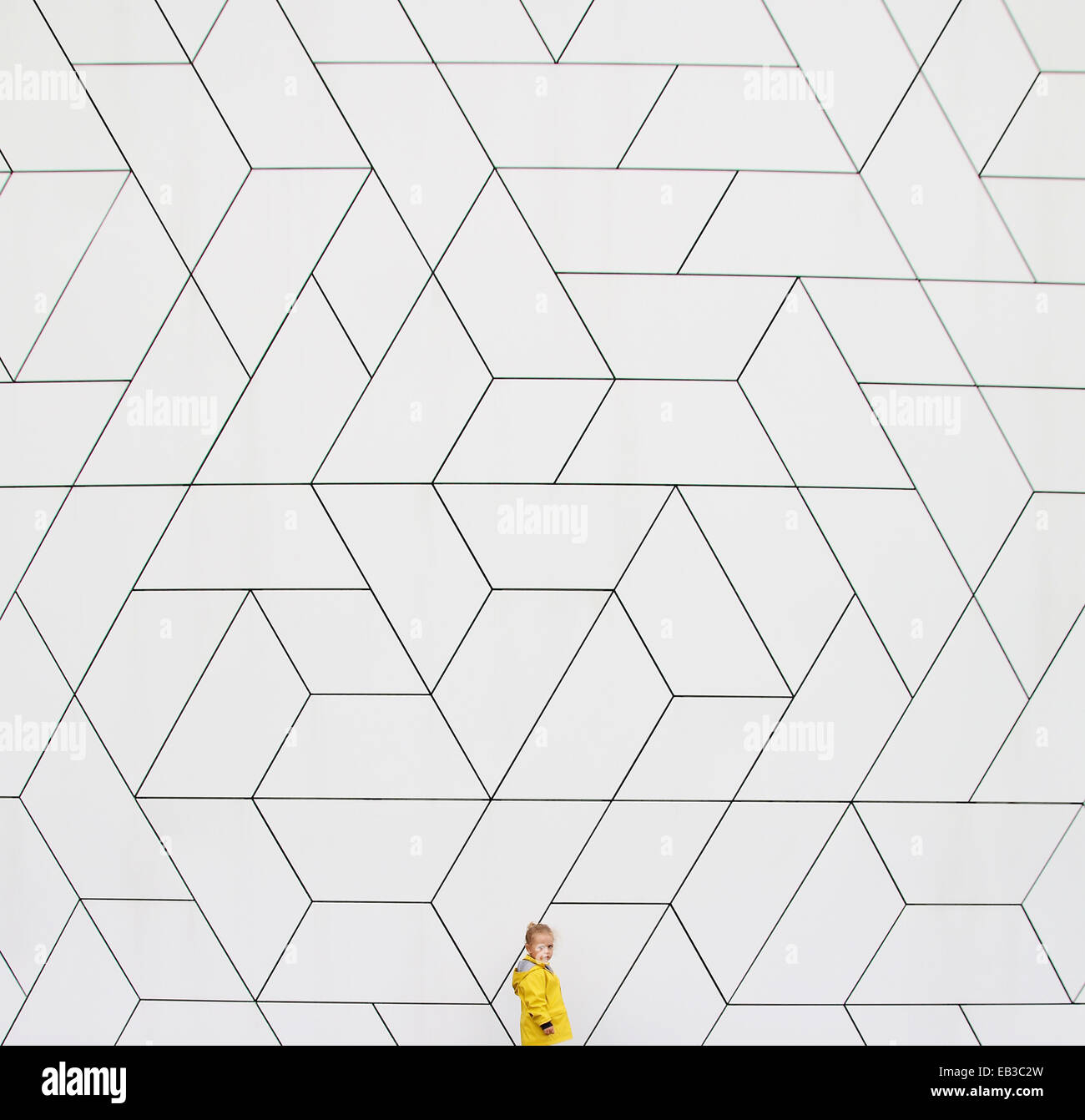 Girl (2-3) in yellow raincoat against white wall - Stock Image