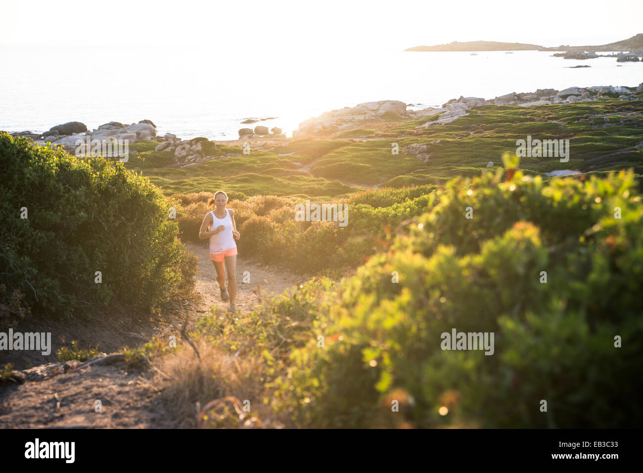 France, Corsica, Woman trail running at coast - Stock Image