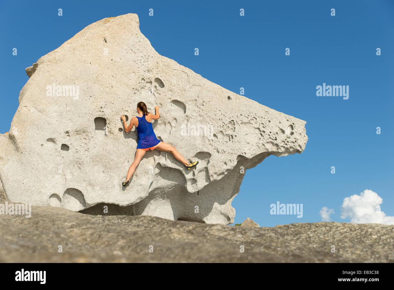 Rear view of a woman climbing a big rock, Corsica, France Stock Photo