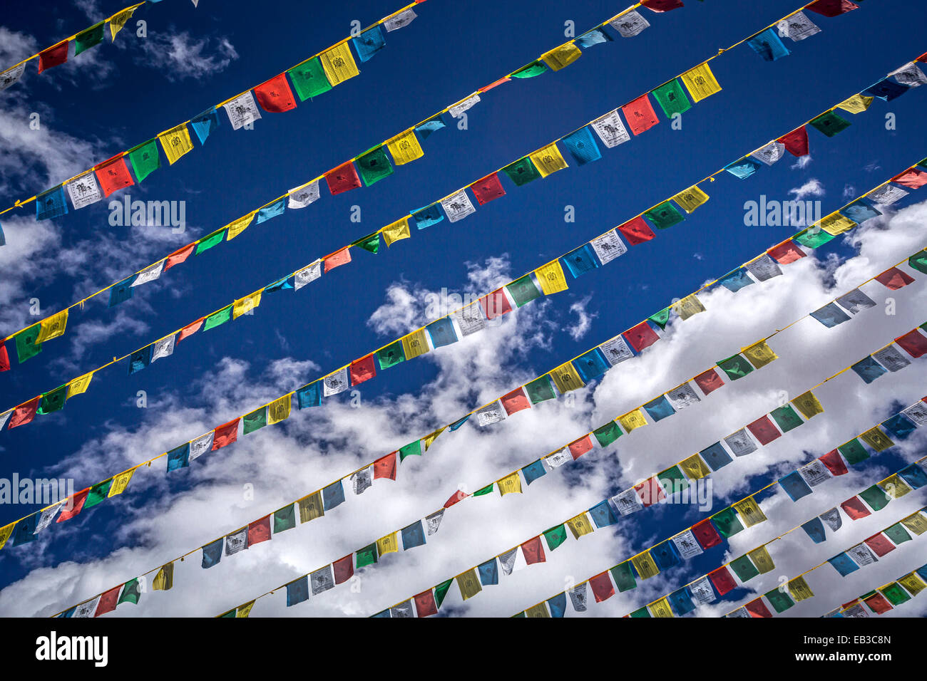 Praying flags in blue sky - Stock Image