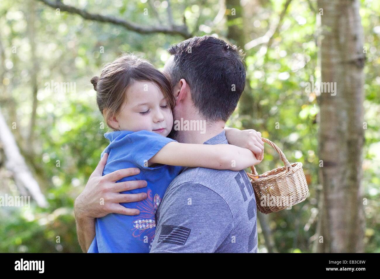 Girl standing in forest hugging her father - Stock Image