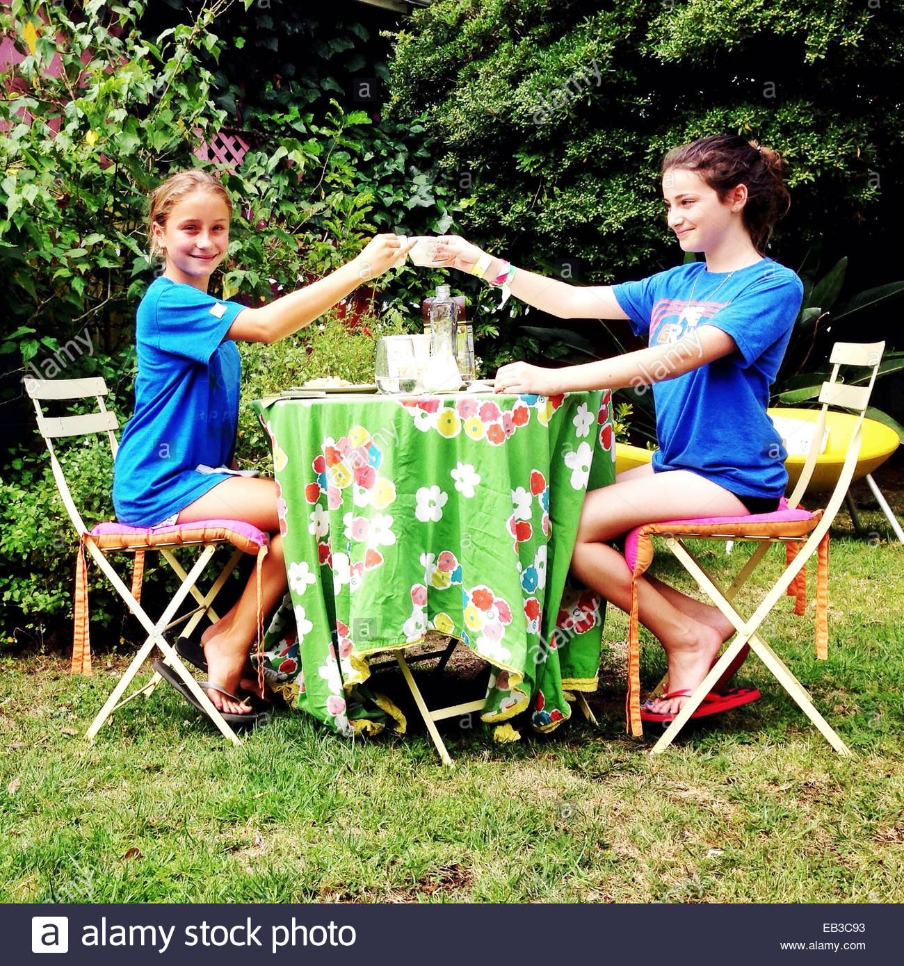 Two girls sitting in garden making a celebratory toast with cups of tea - Stock Image