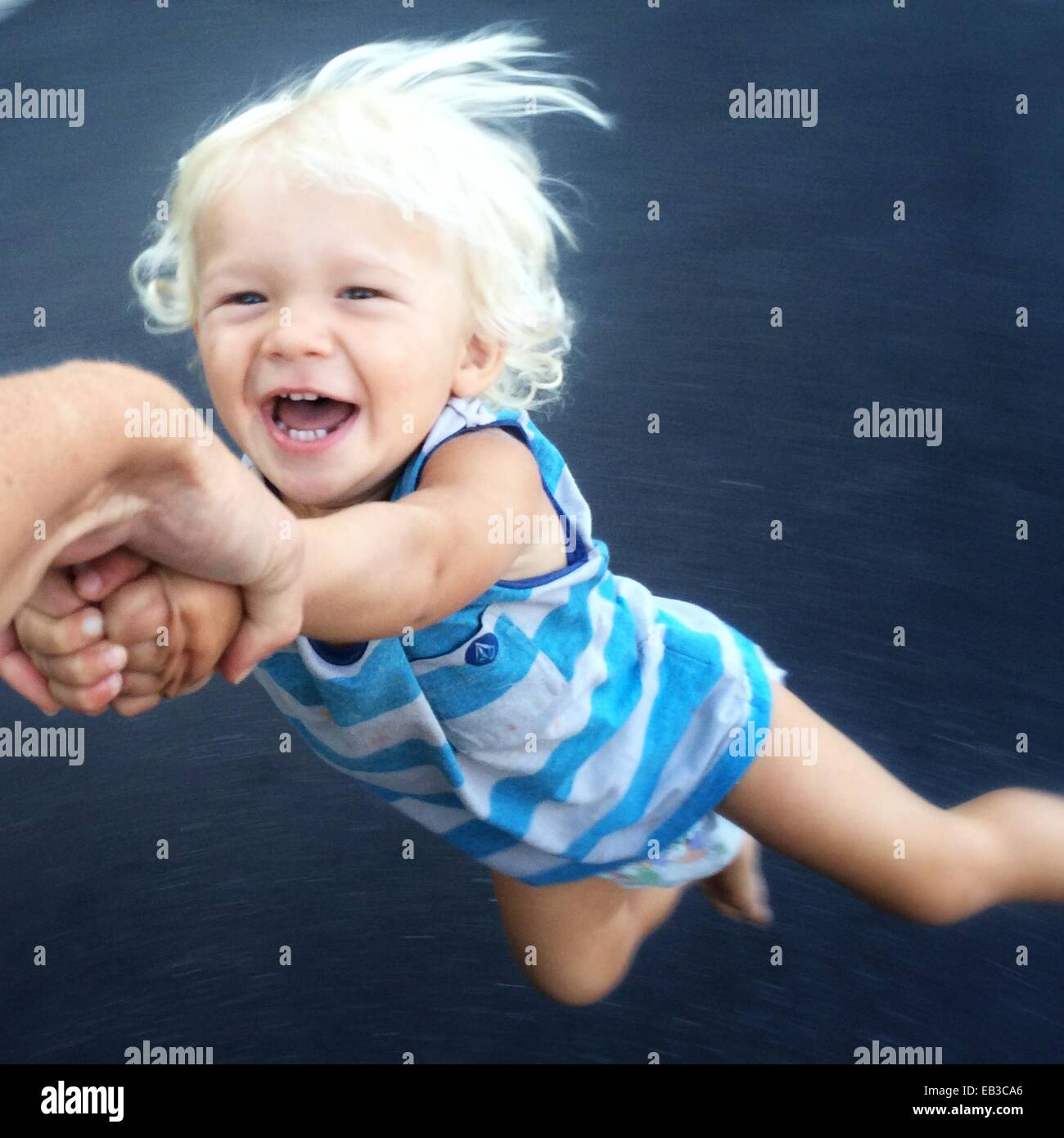 Toddler being spun around - Stock Image