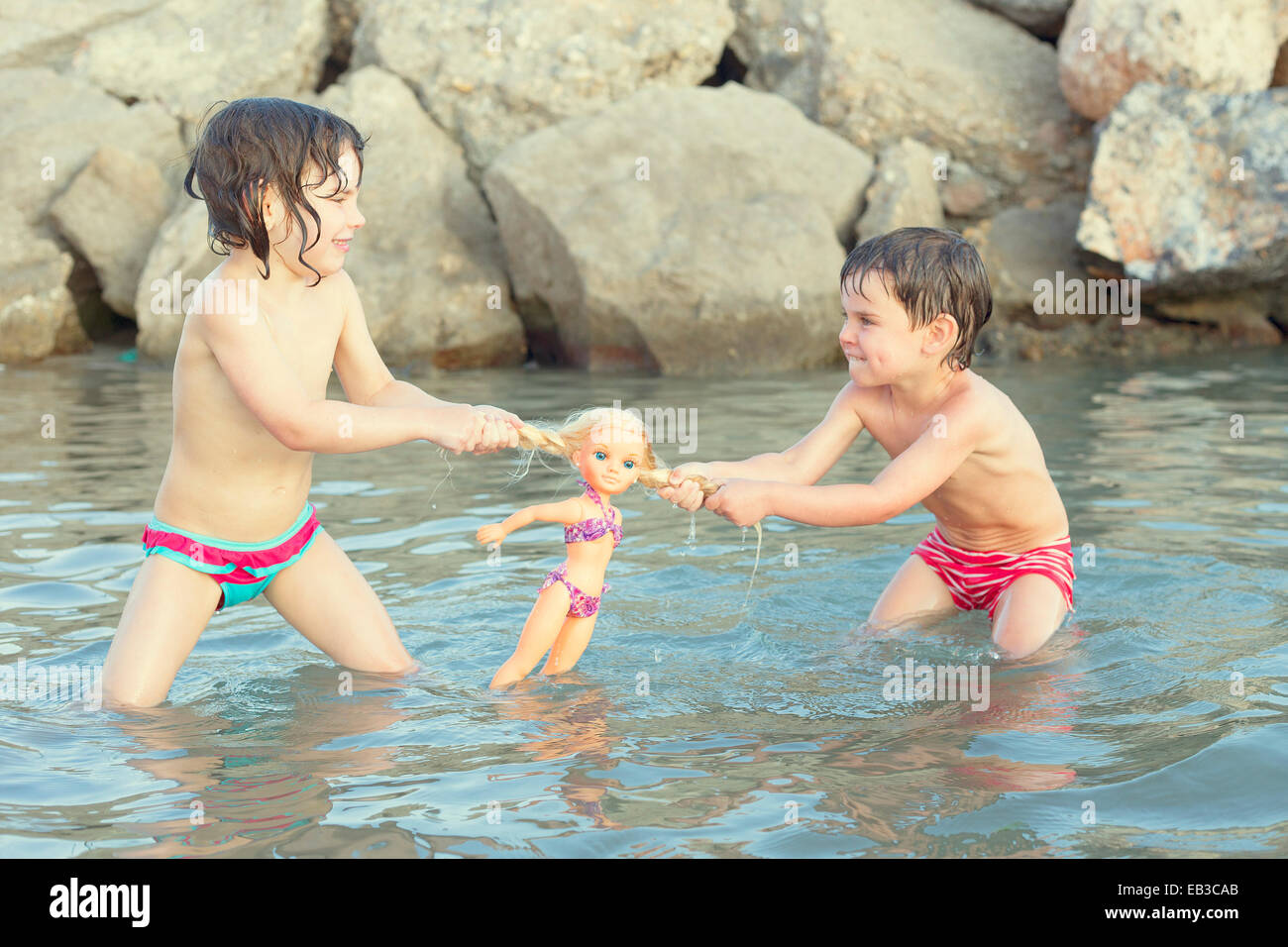 Girl and boy standing in lake fighting over doll - Stock Image