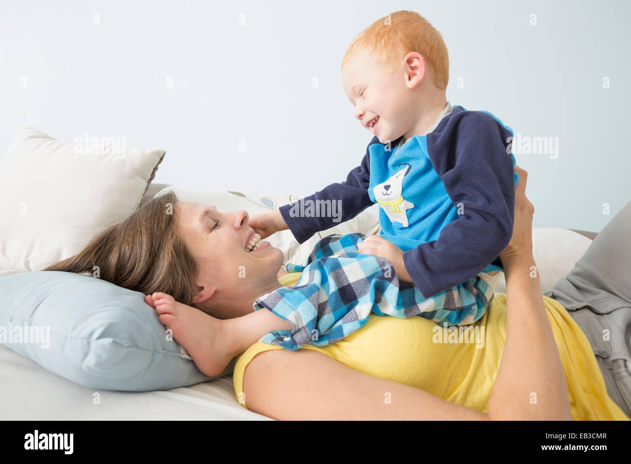 Caucasian mother and son playing on bed Stock Photo