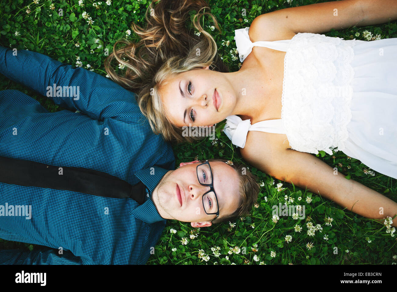 USA, Minnesota, Hennepin County, Minneapolis, Overhead view of young couple lying on grass - Stock Image