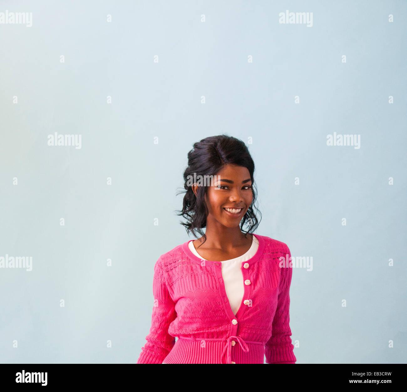 Studio portrait of smiling mid adult woman wearing pink cardigan - Stock Image