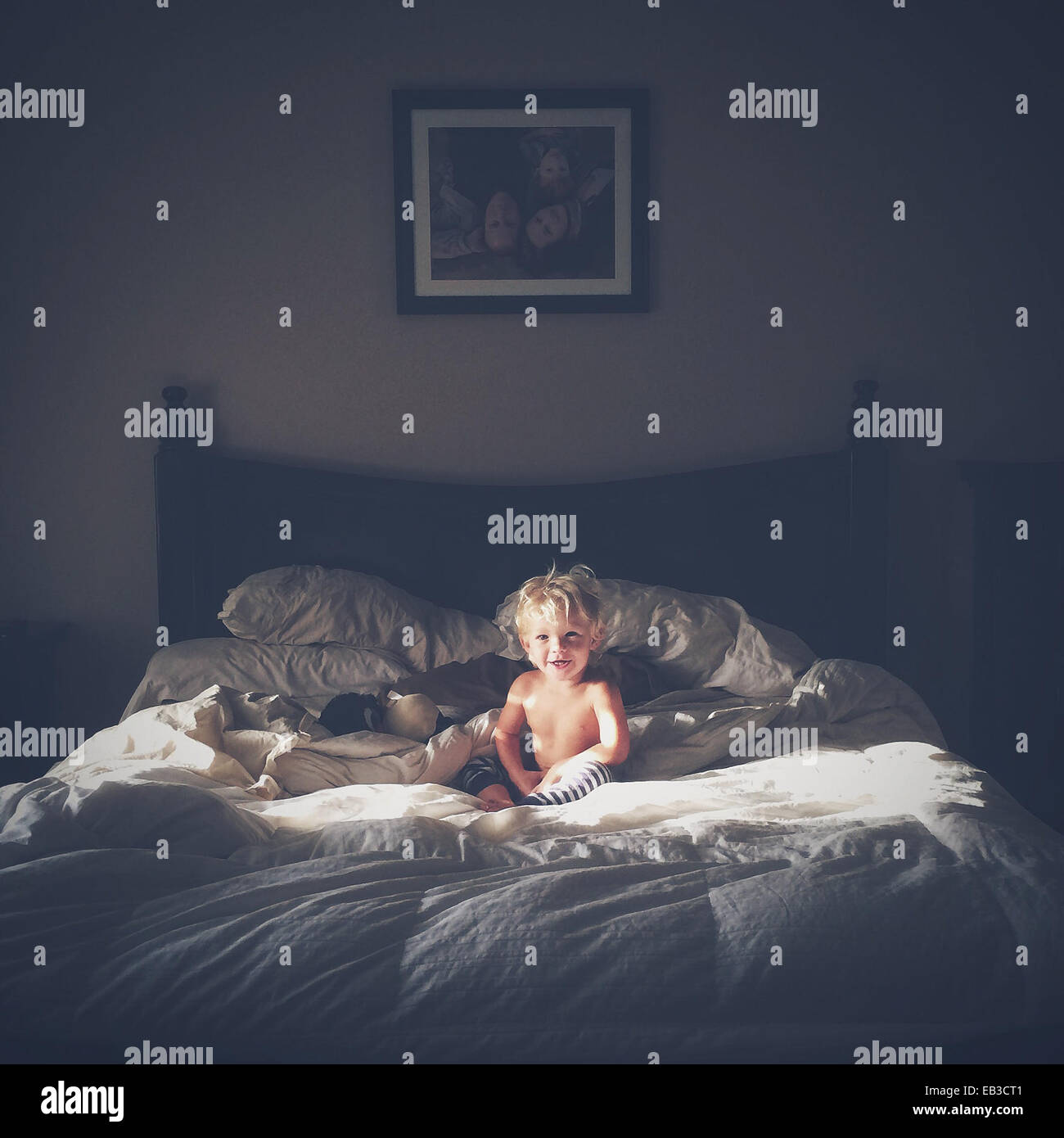 Portrait of laughing baby boy sitting on messy bed - Stock Image