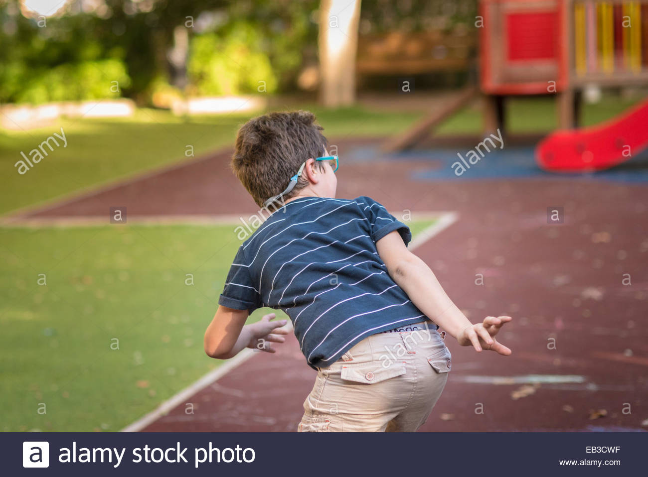 Spain, Valencia, Boy(8-9) playing hide-and-seek in playground Stock Photo