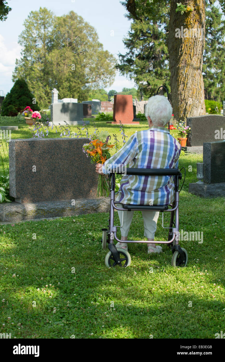 Older Caucasian woman visiting grave in cemetery Stock Photo