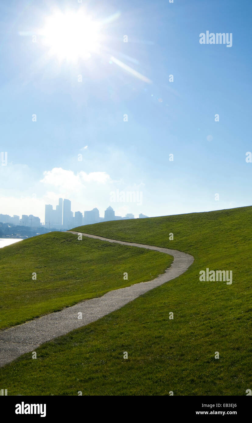 Sun shining over paved road on grassy hillside, Seattle, Washington, United States - Stock Image