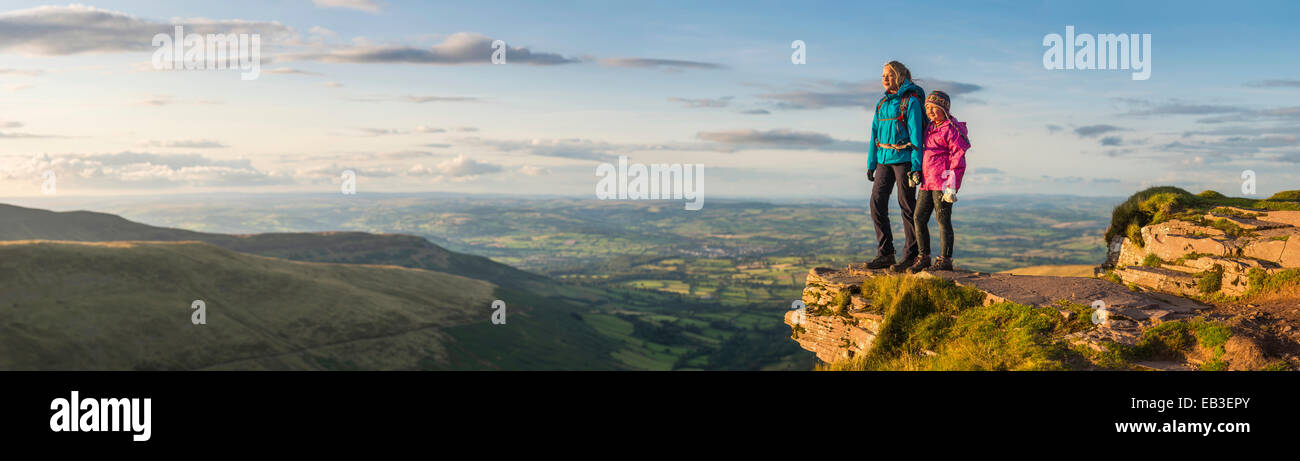Panoramic view of hikers overlooking remote landscape - Stock Image