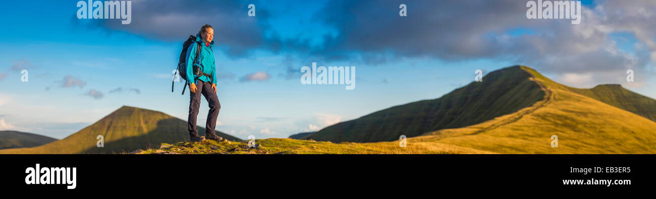 Panoramic view of hiker walking up grassy hill - Stock Image