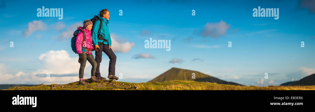 Panoramic view of hikers walking up grassy hill - Stock Image