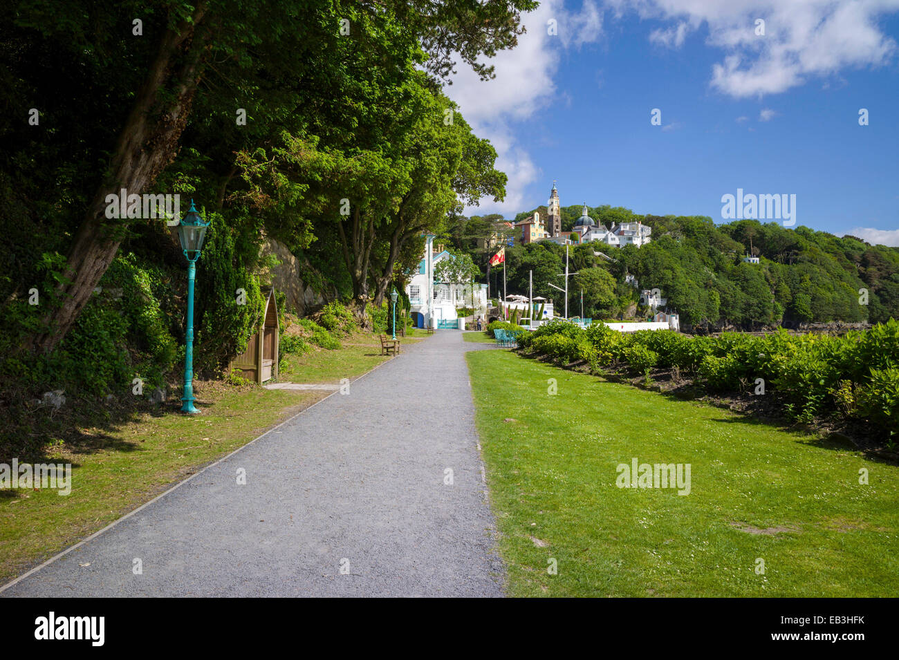 Portmeirion Hotel, quayside walk, Portmeirion village in the wooded background, on the estuary of the river Dwyryd. - Stock Image
