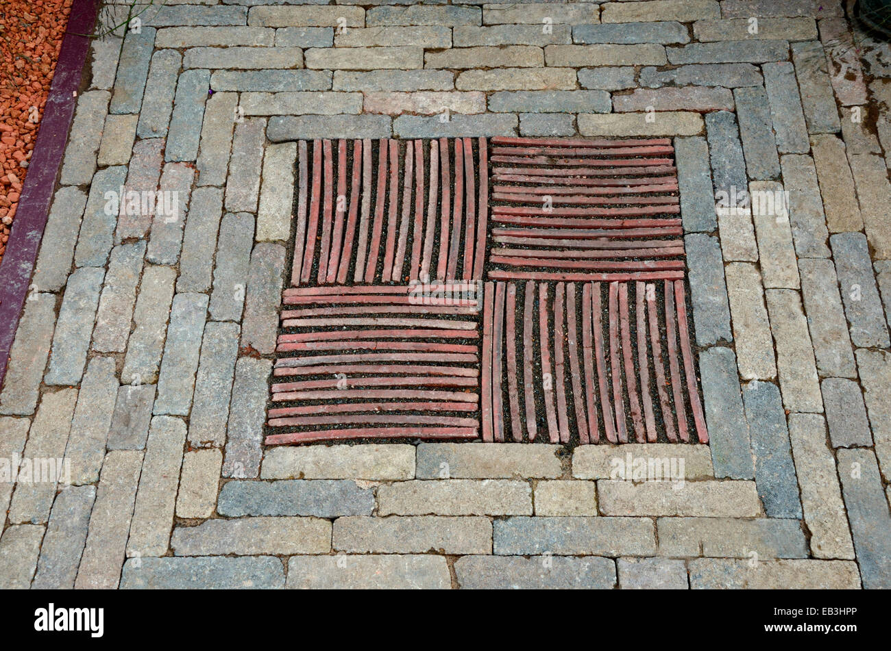 A close up view of decorative mosaic insert of stones bricks and tiles in a garden pathway - Stock Image