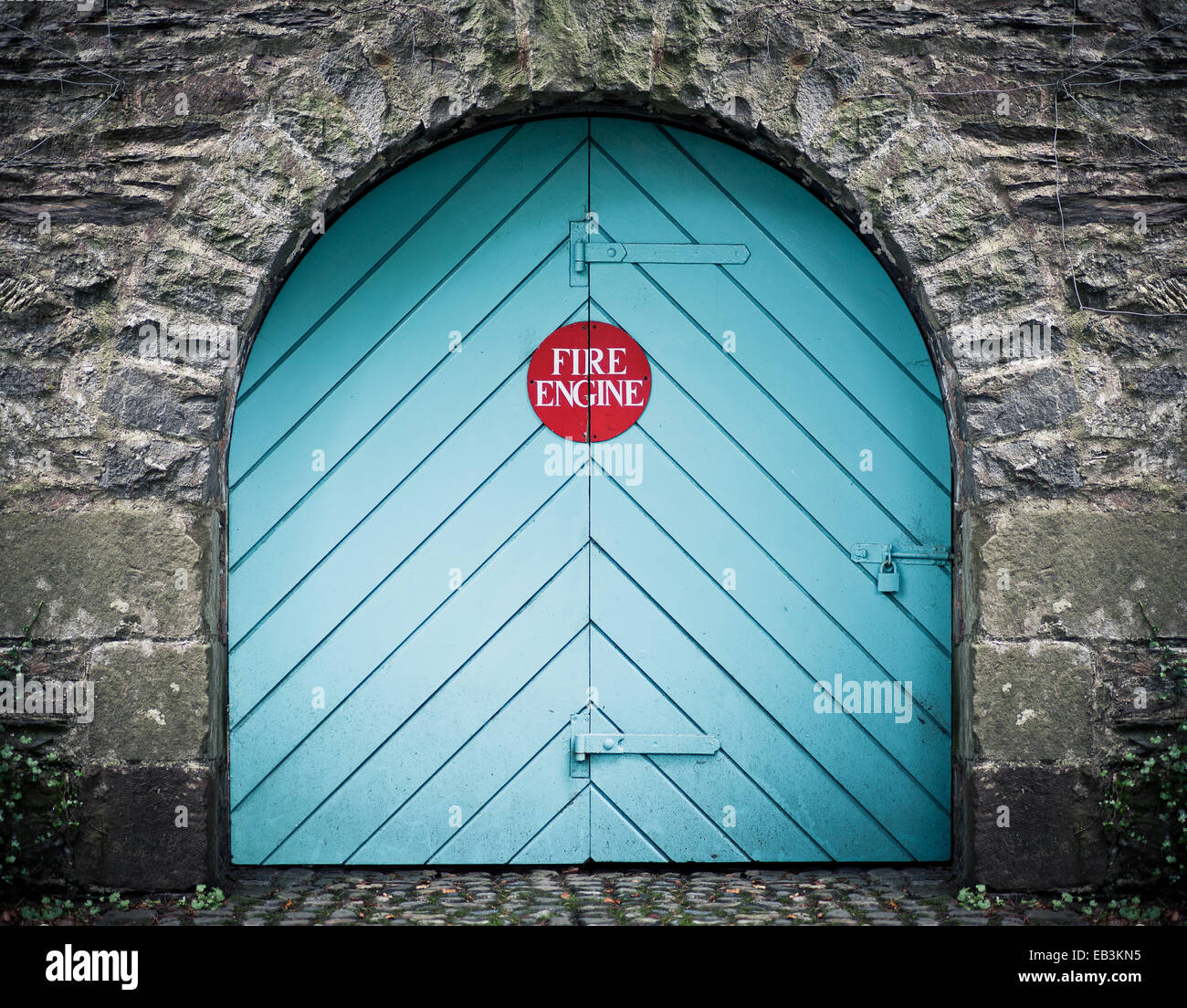 fire station, fire engine blue door at portmerion north wales uk, unusual fire engine sign on the door - Stock Image