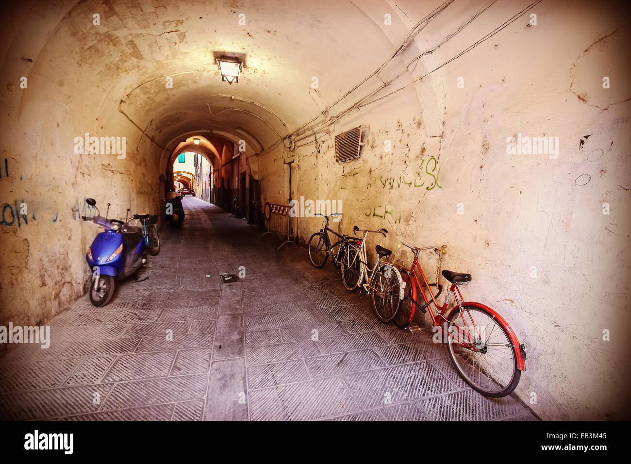 Retro filtered picture of neglected passage with bikes. - Stock Image