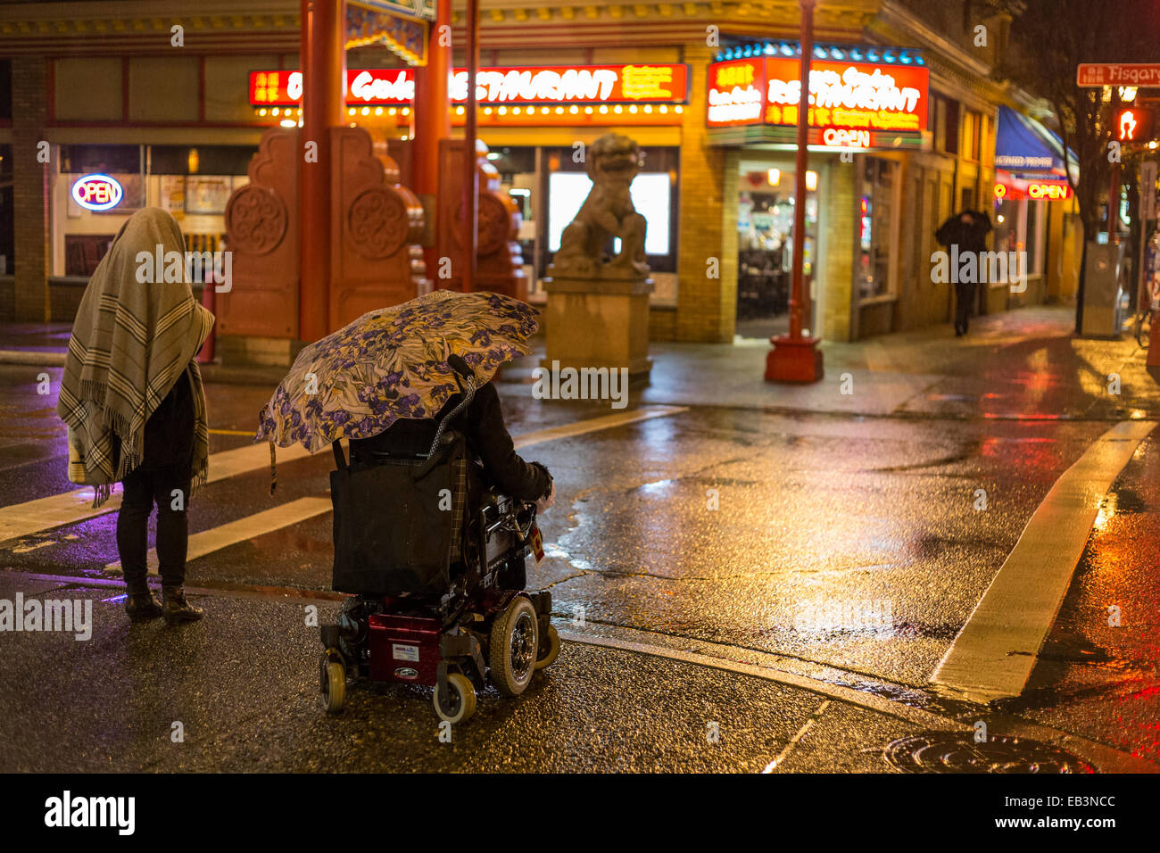 Disabled man in wheelchair with umbrella in Chinatown on rainy night-Victoria, British Columbia, Canada. - Stock Image