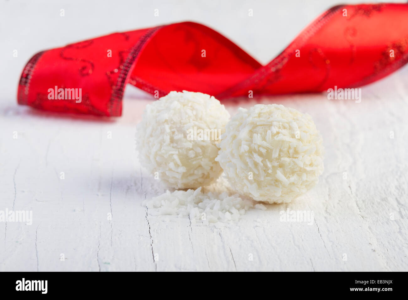 Coconut snowball truffles on white background. Arrangement of coconut cookies on wooden elegant background. - Stock Image