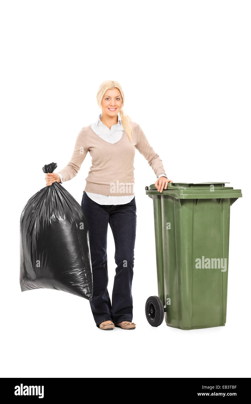 Full length portrait of a woman holding a trash bag next to a garbage bin isolated on white background - Stock Image