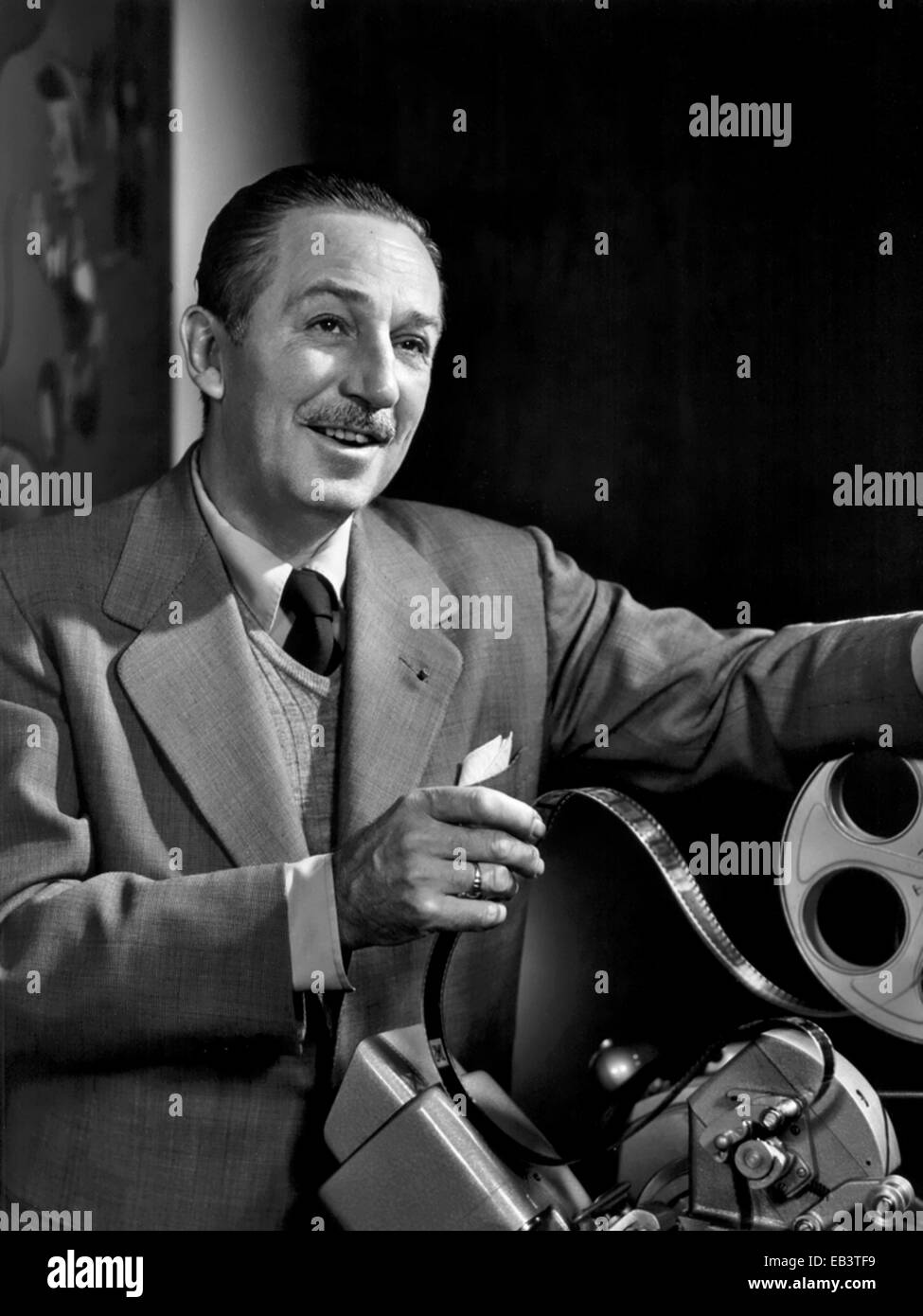 Portrait of Walt Disney looking over footage in the movieola editing machine at Disney Studios December 1954. Walt Stock Photo