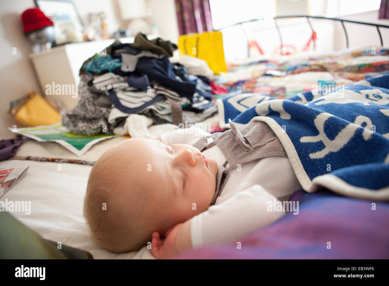 Baby sleeping with piles of laundry in background - Stock Image