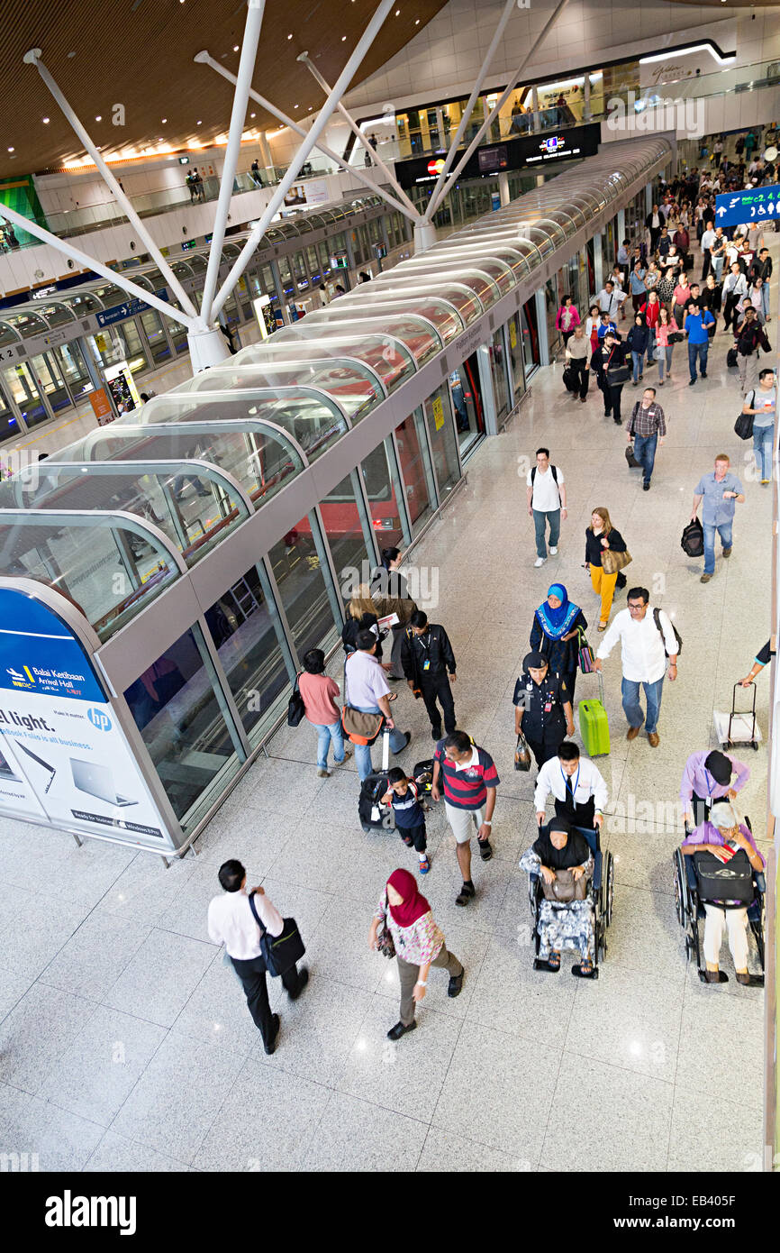 People arriving in concourse using transport system, Kuala Lumpur international airport, Malayisa - Stock Image