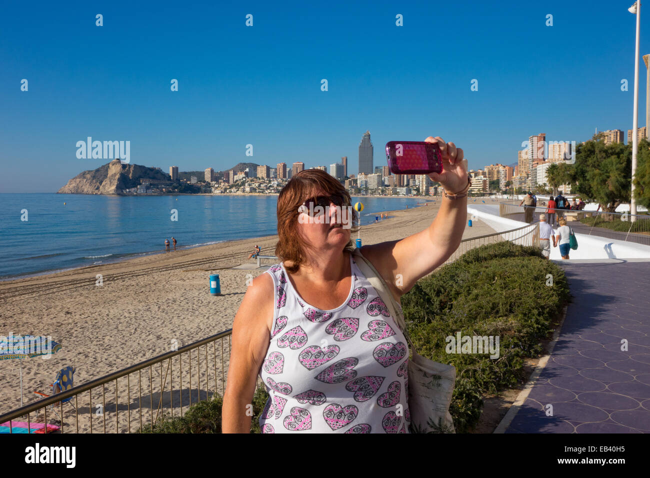 Benidorm, Costa Blanca, Spain, Europe. Woman tourist taking selfie selfy on promenade, with cell, mobile phone. - Stock Image