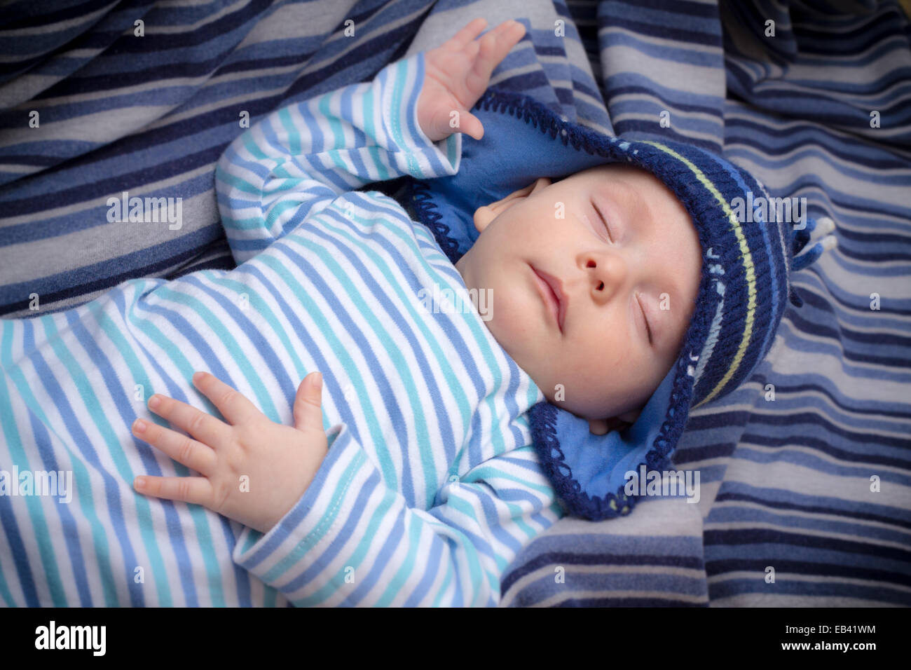 Newborn baby boy with striped hat and pajama sleeping on a blue blanket 718a4fa52405