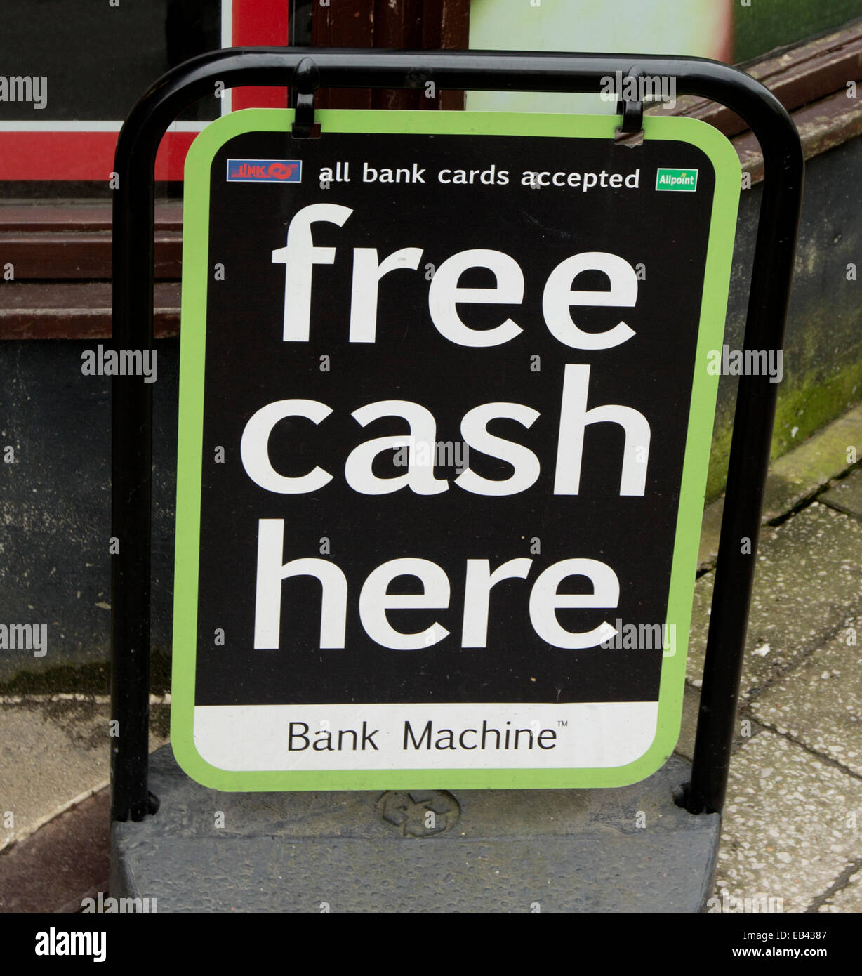 Humourous sign on footpath outside bank, 'Free Cash Here', that, taken literally, means cash is being given - Stock Image