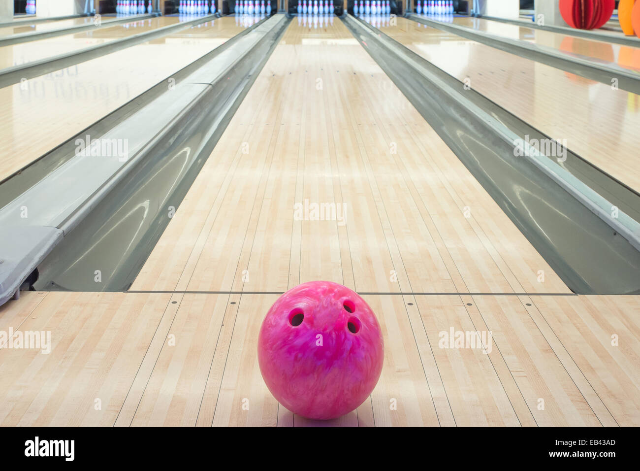 Balls on bowling alley against ten pins - Stock Image