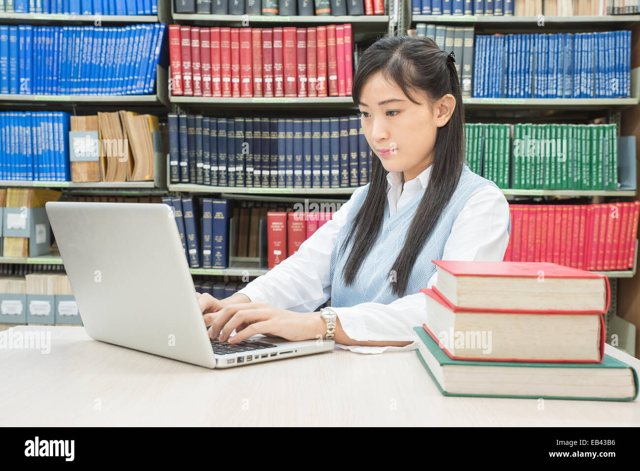 Asian female student typing on notebook in library - Stock Image