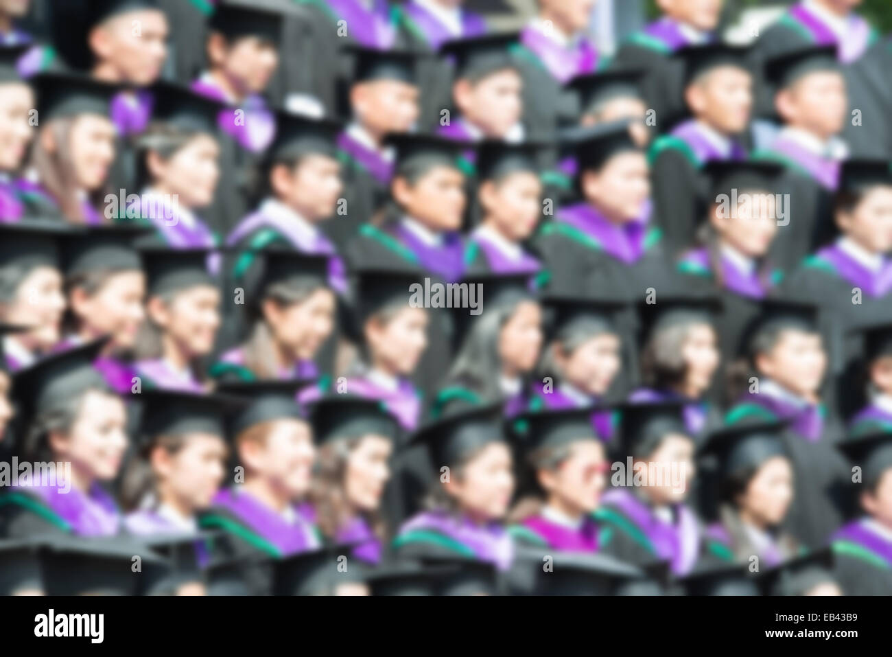Shot of graduation caps during commencement. The image was blurred for use as a background. - Stock Image