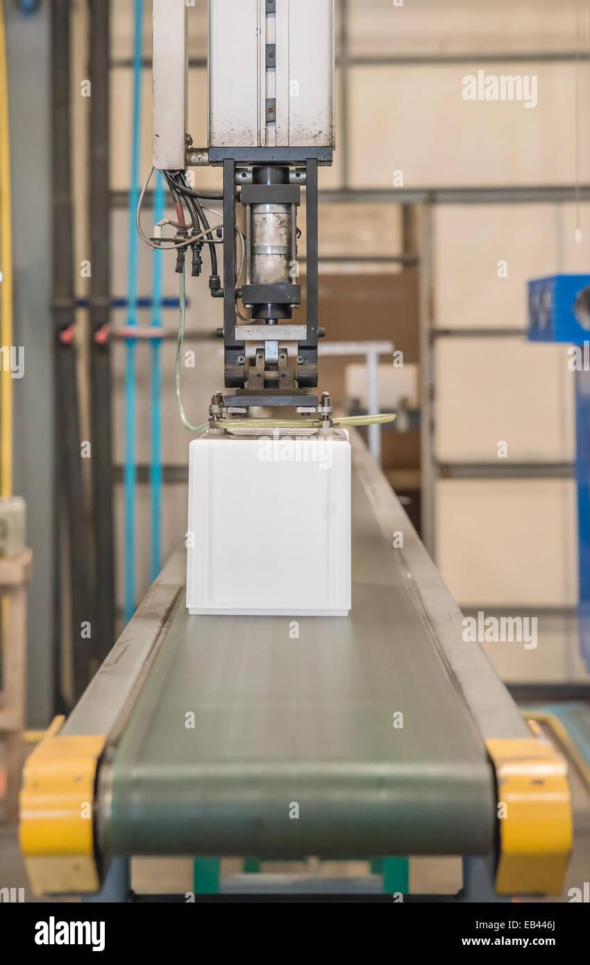 Industrial robot working in plastic factory - Stock Image