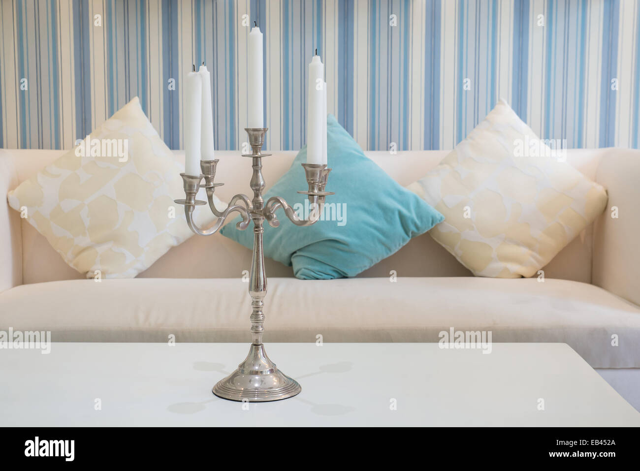 candlestick with five  candles on table with sofa in background - Stock Image