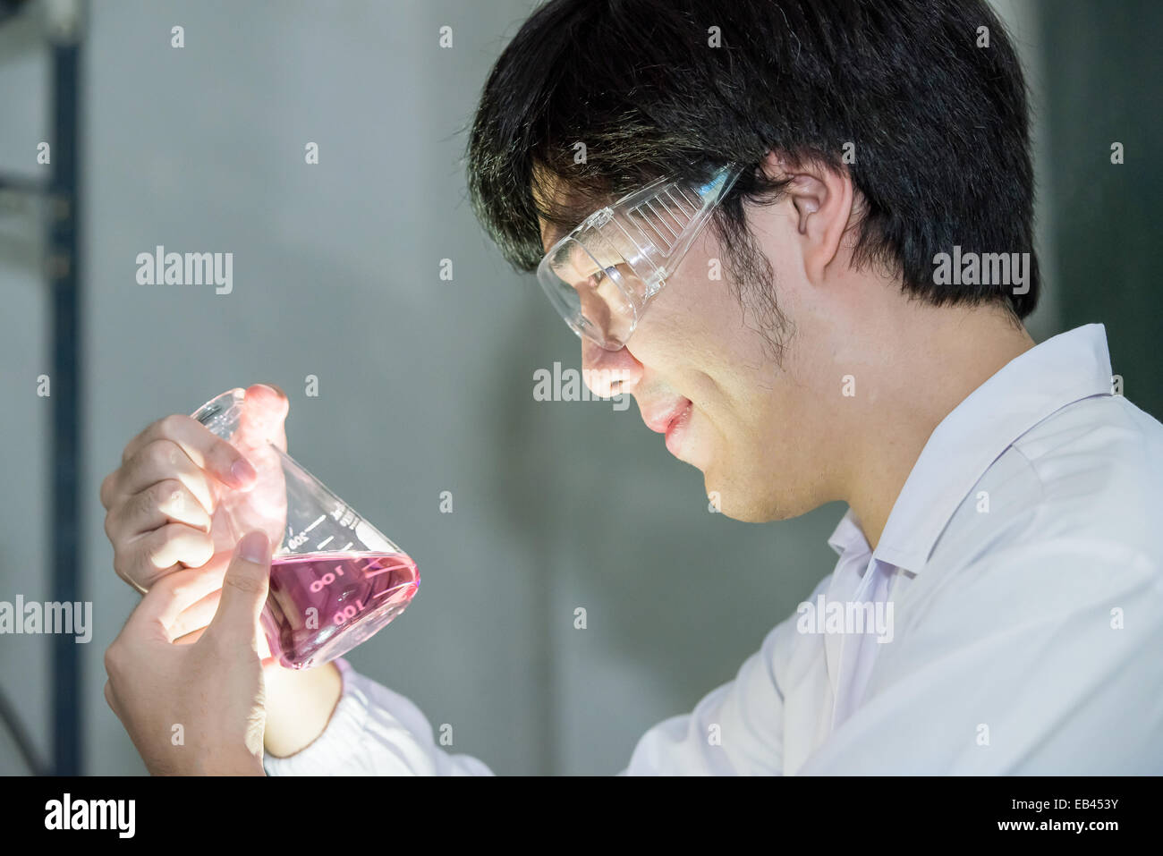 Asian scientist in white uniform looking at a test beaker in laboratory - Stock Image