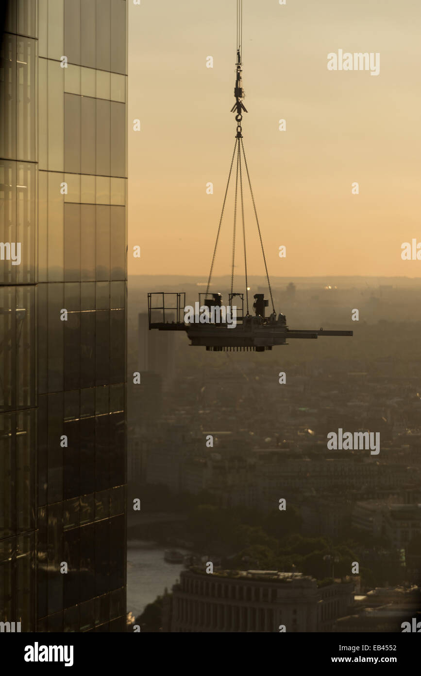 Maintenance platform being lifted by crane on the Cheesegrater during construction. - Stock Image