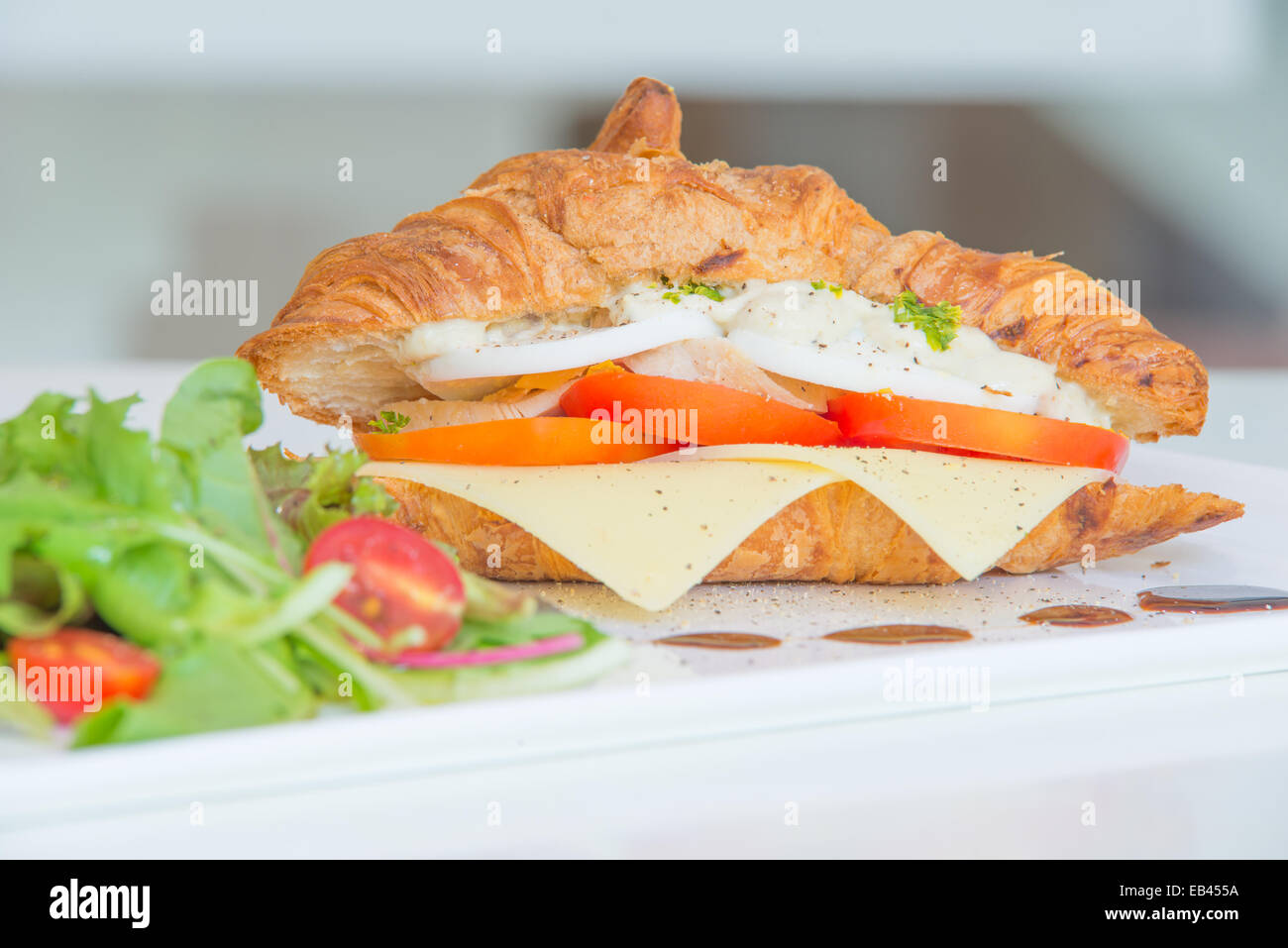 Croissant with cheese tomato chicken and salad - Stock Image